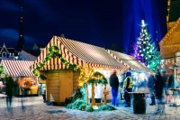 Strolling and visiting while shopping at Riga's Christmas Market. The candy cane-striped booths and brightly illuminated Christmas tree make evenings a wonderful time to visit.