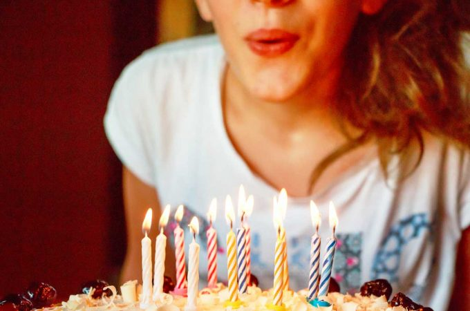 woman-blowing-out-candles-on-birthday-cake